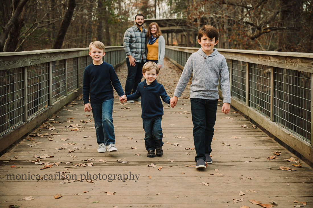 three brothers walk hand in hand while their parents watch on the bridge at McDaniel Family Farm