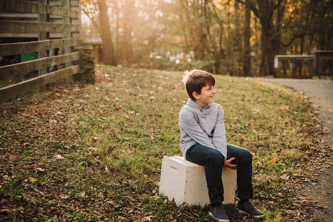 tween boy looks away while siting on a antique block in Duluth, GA