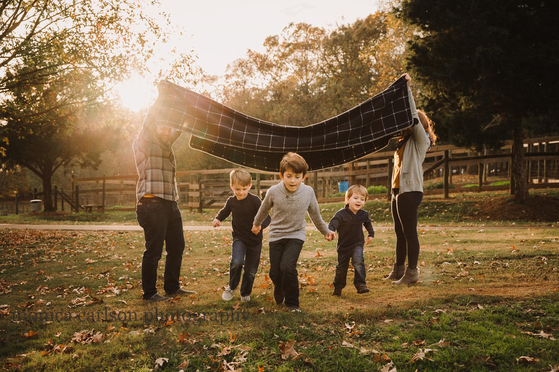 family of five play a game with a blanket during a family photo session