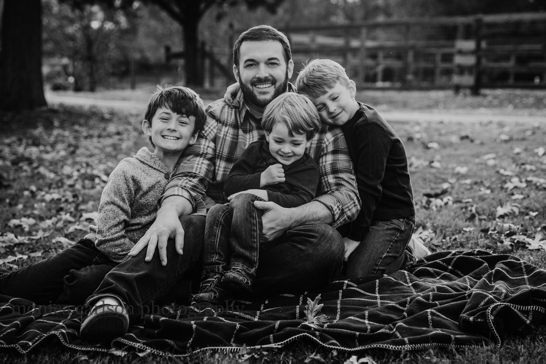 father snuggles with his three young sons during a photo session with monica carlson