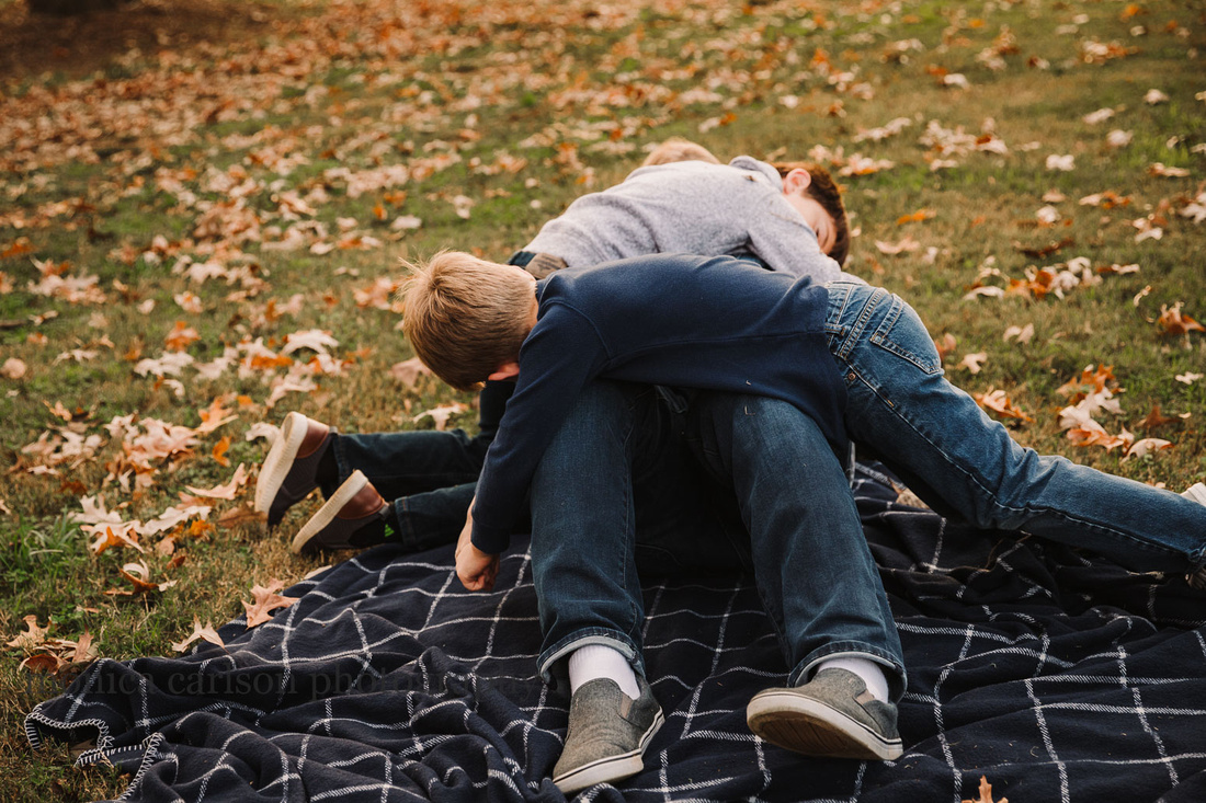 father is tackled by his three young sons by monica carlson photography