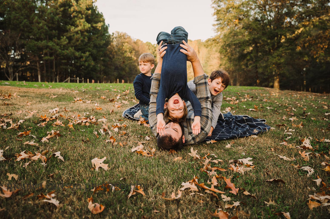 father holds one of his three sons upside down while they play in the grass