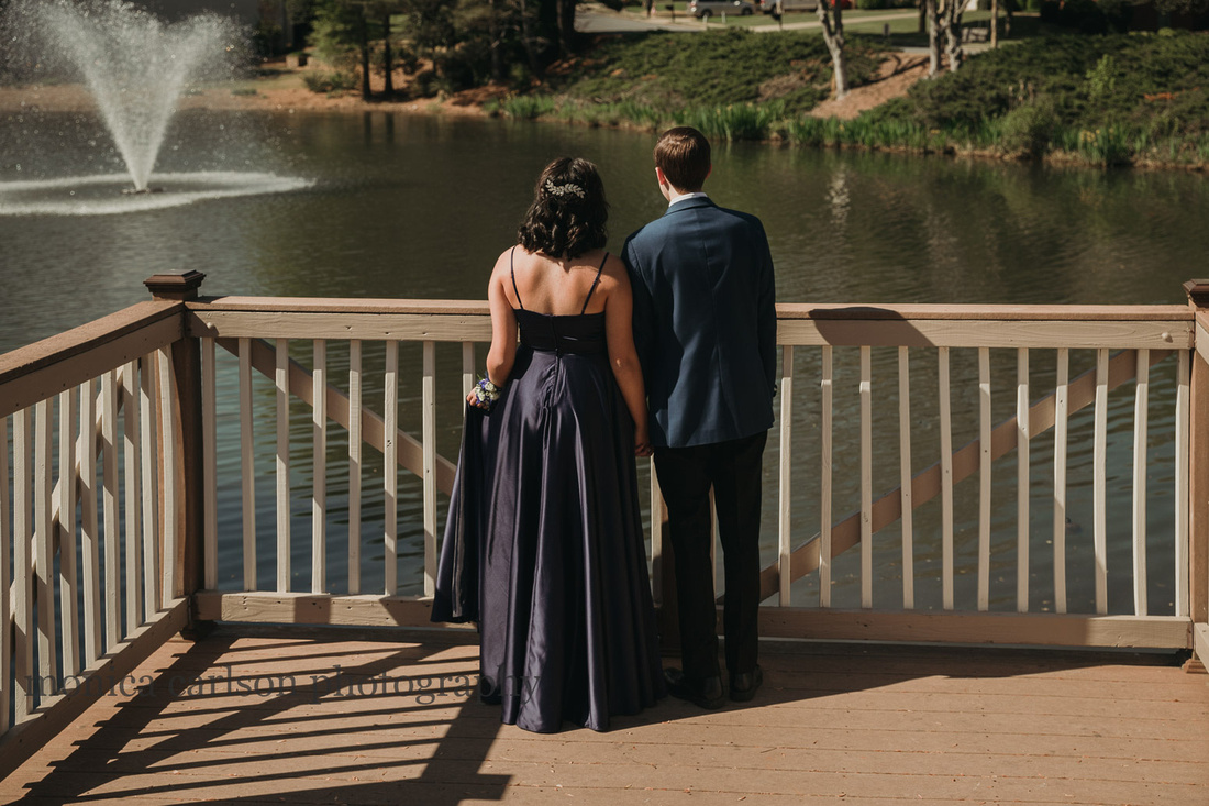 drressed up young couple look out over a lake before their first prom