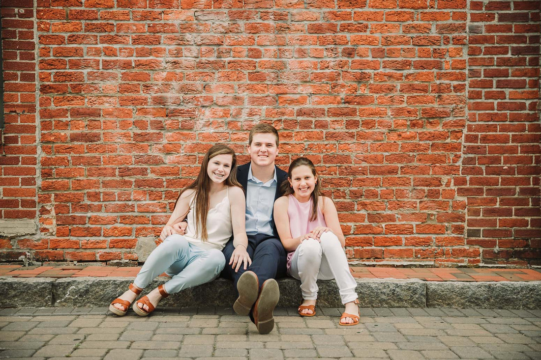 portrait of three teen siblings seated in front of brick building for a family photo session