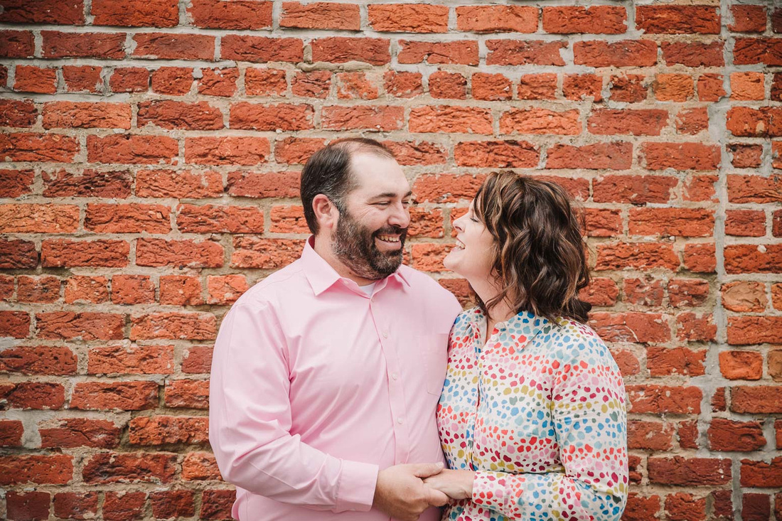 husband and wife laugh together during a family photo session with monica carlson