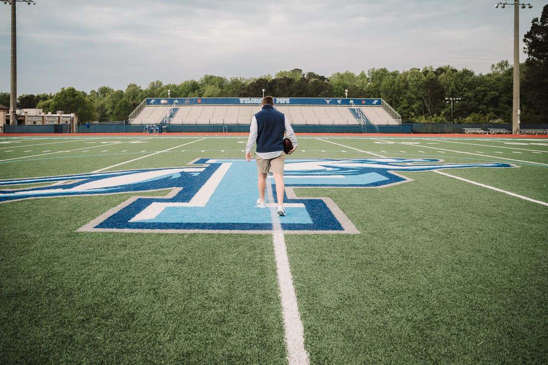 teen walking across the football field at Pope High school