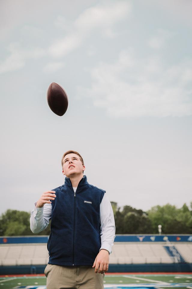 senior boy tossing a footbal at his schools stadium during his senior photo session