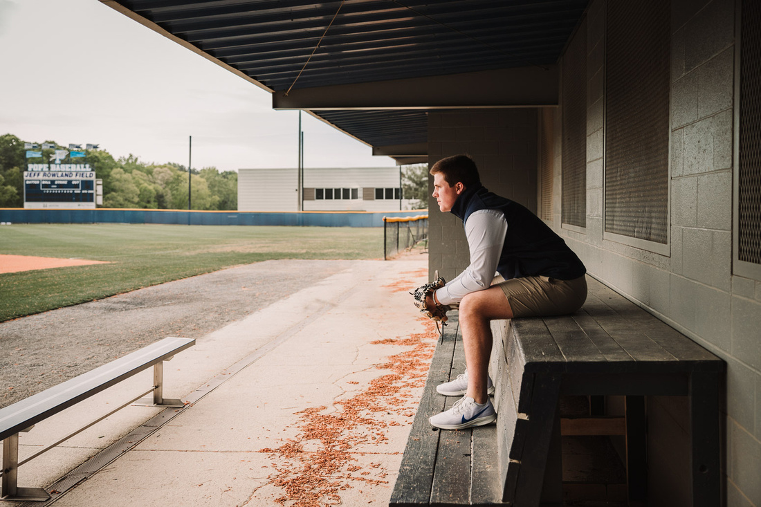 Senior boy sitting in the dug out at Pope High school's stadium