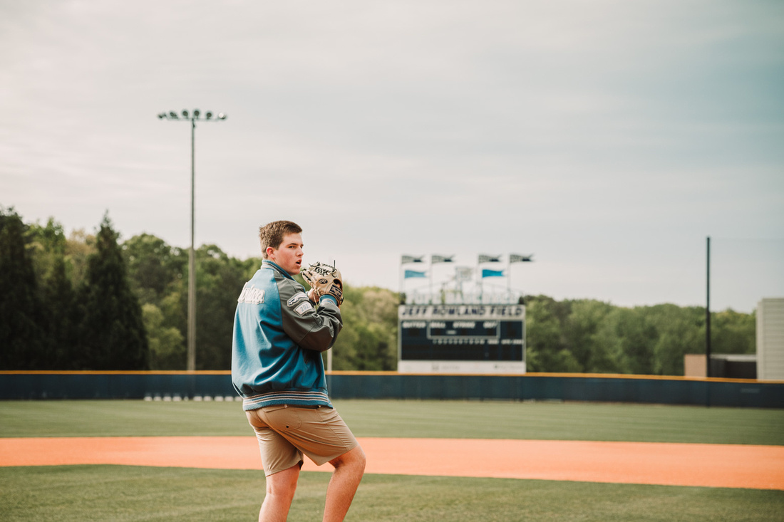 senior  boy throwing a ball at the baseball field during a senior photo session by monica carlson