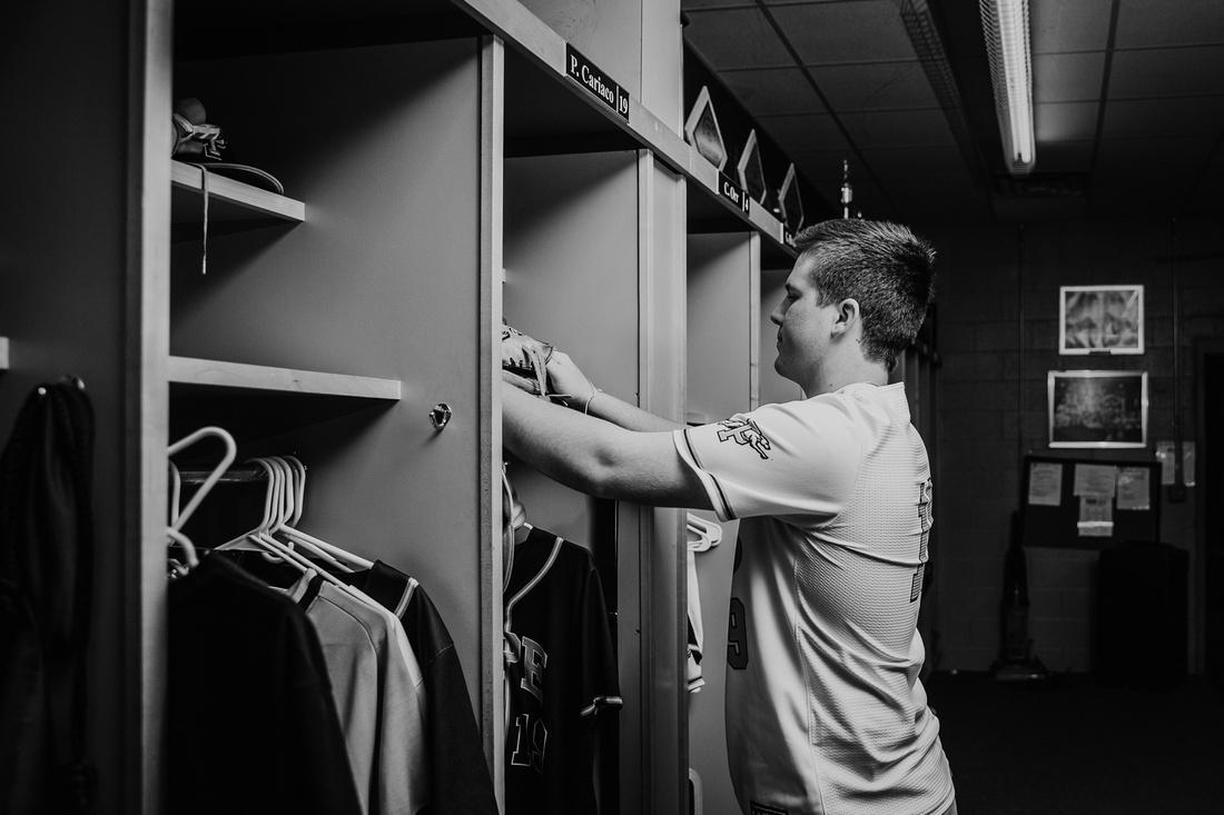 senior putting things in his locker by monica carlson