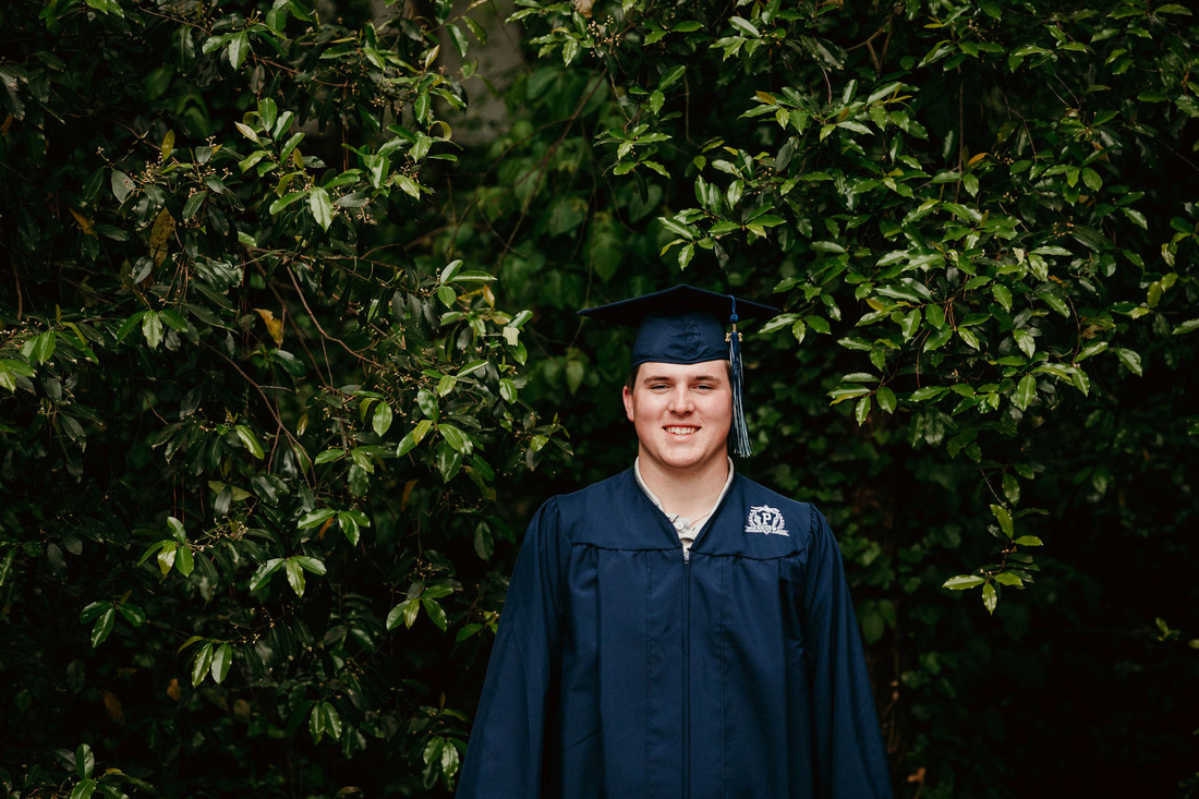 senior boy smiling for a cap and gown image by monica carlson photography