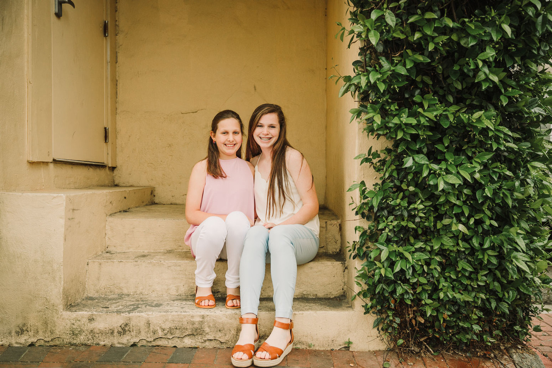 sisters sitting together by a yellow wall and greenery during a family photo session in Marietta, GA