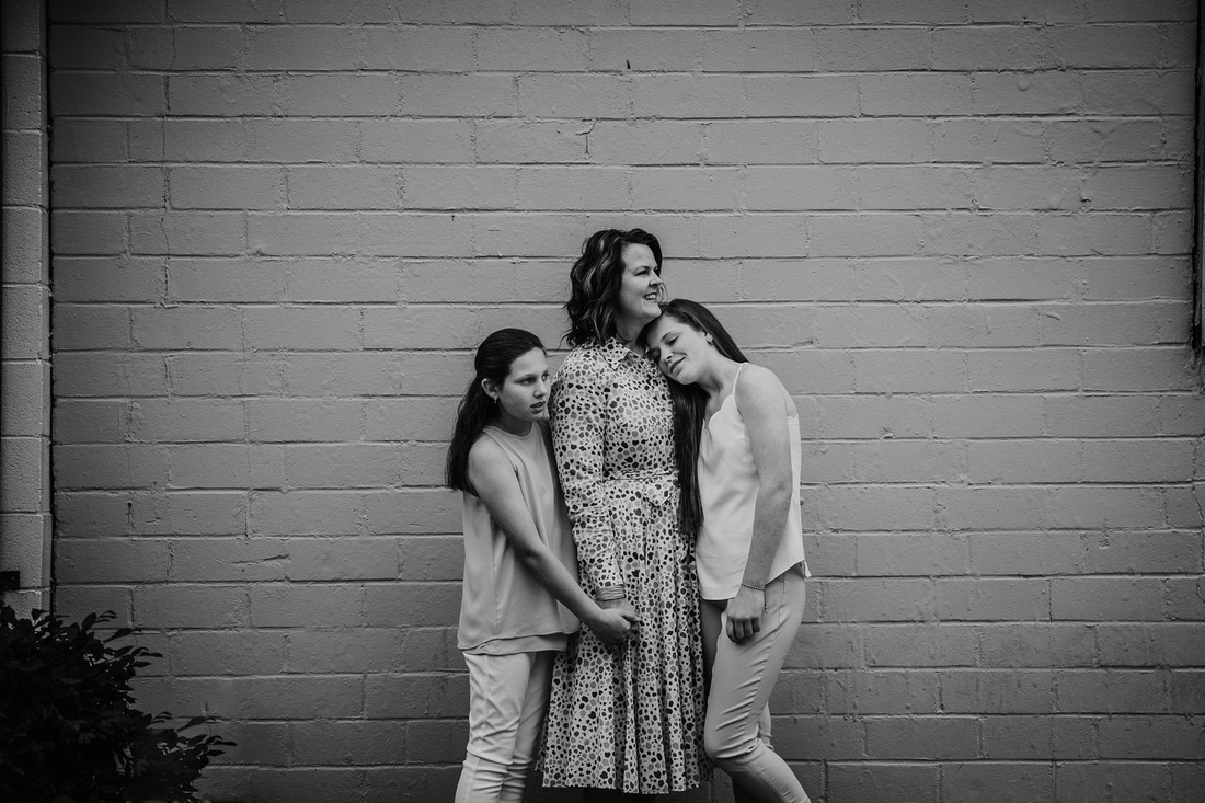Mother cuddling her teen daughters during a family photo session