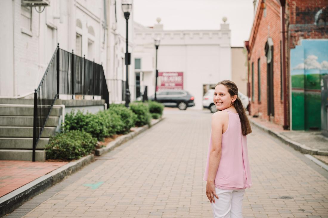 tween looking over her shoulder on a brick street in Marietta, GA