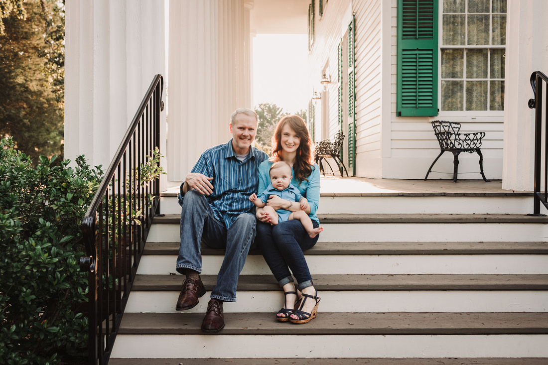 family of three siting on the patio at Barrington Hall during a family photo session