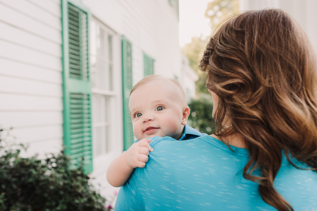 baby boy peeking over his mothers shoulder by monica carlson