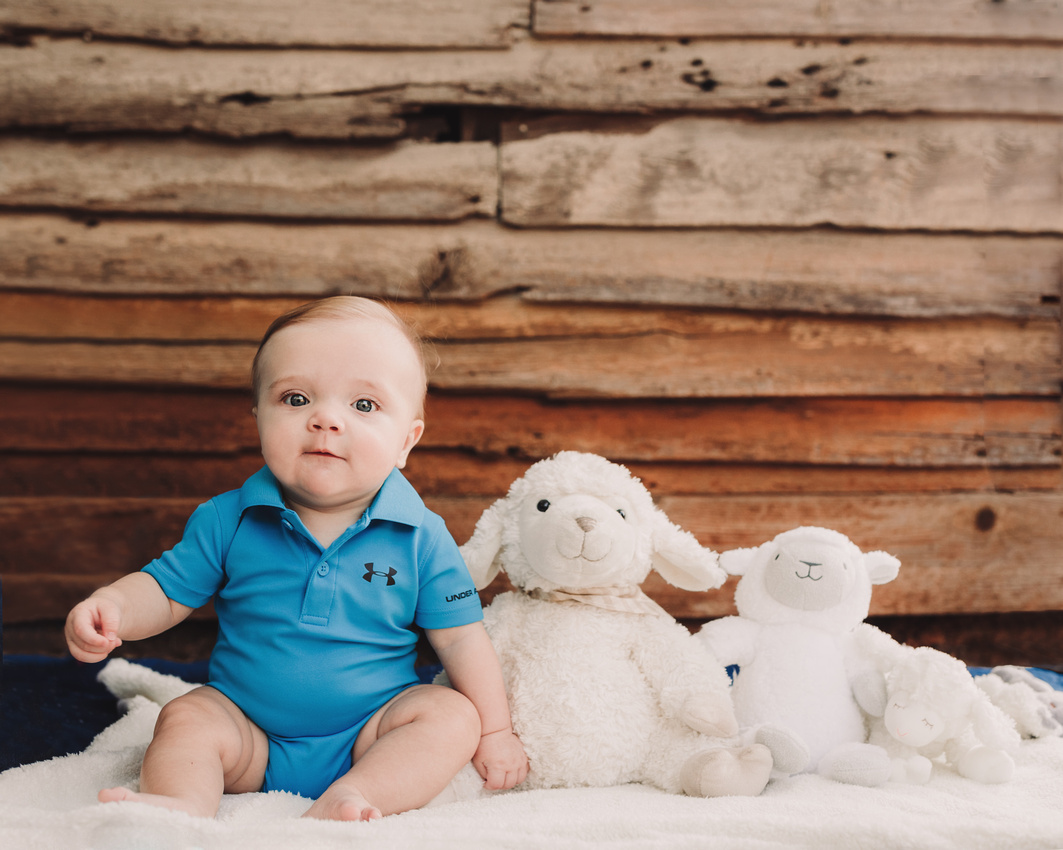 Baby boy with his lamb lovies in front of a wooden building