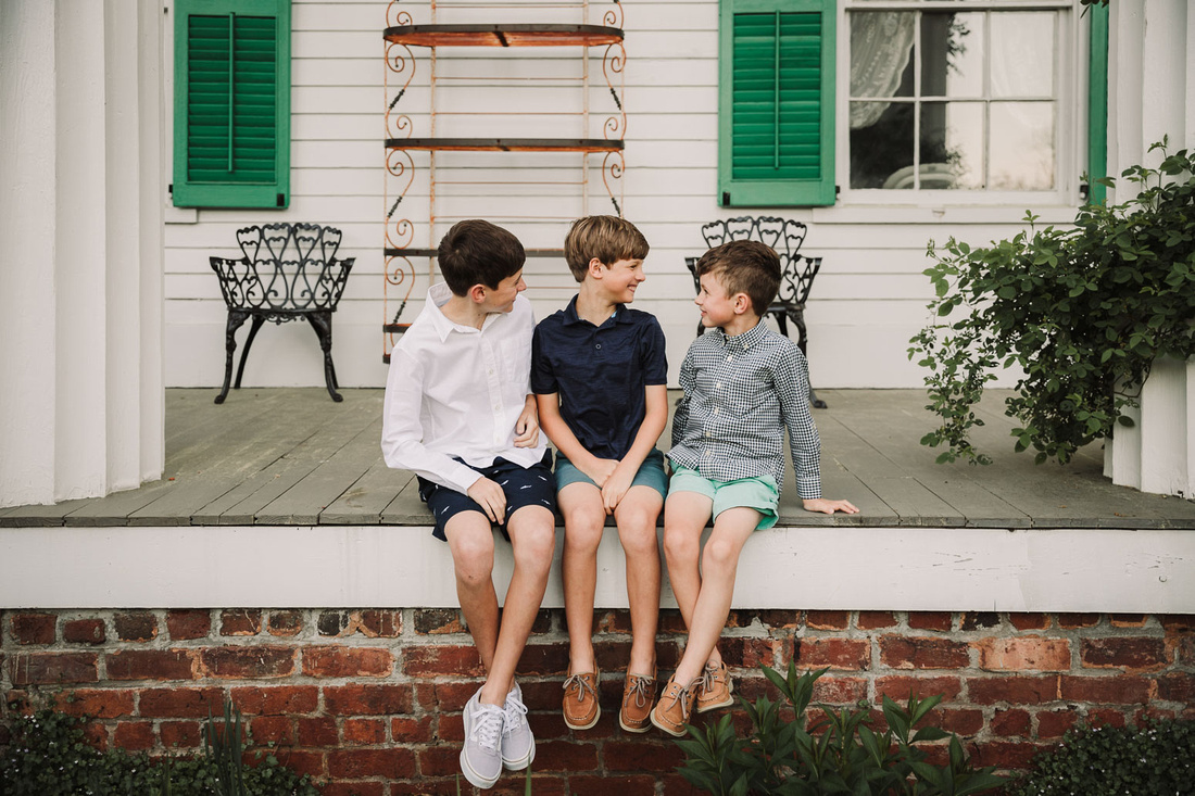 three brothers laughing together on the patio of a historic home