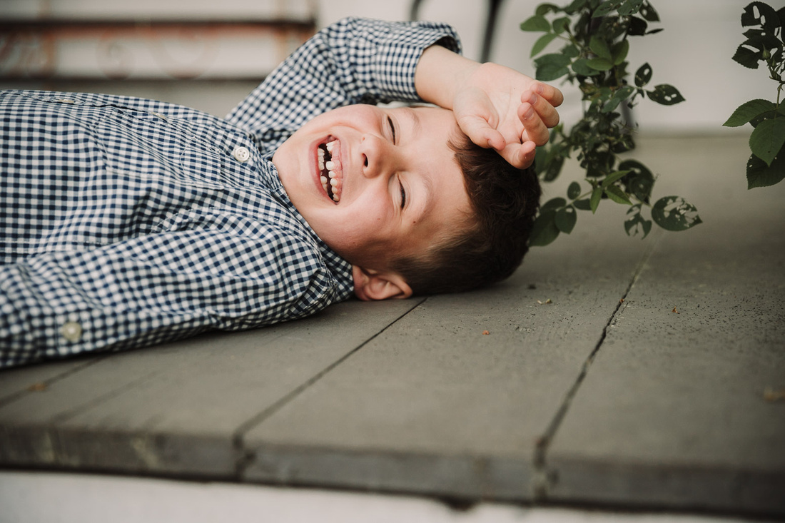 toothless litlle boy laughs so hard he lays down