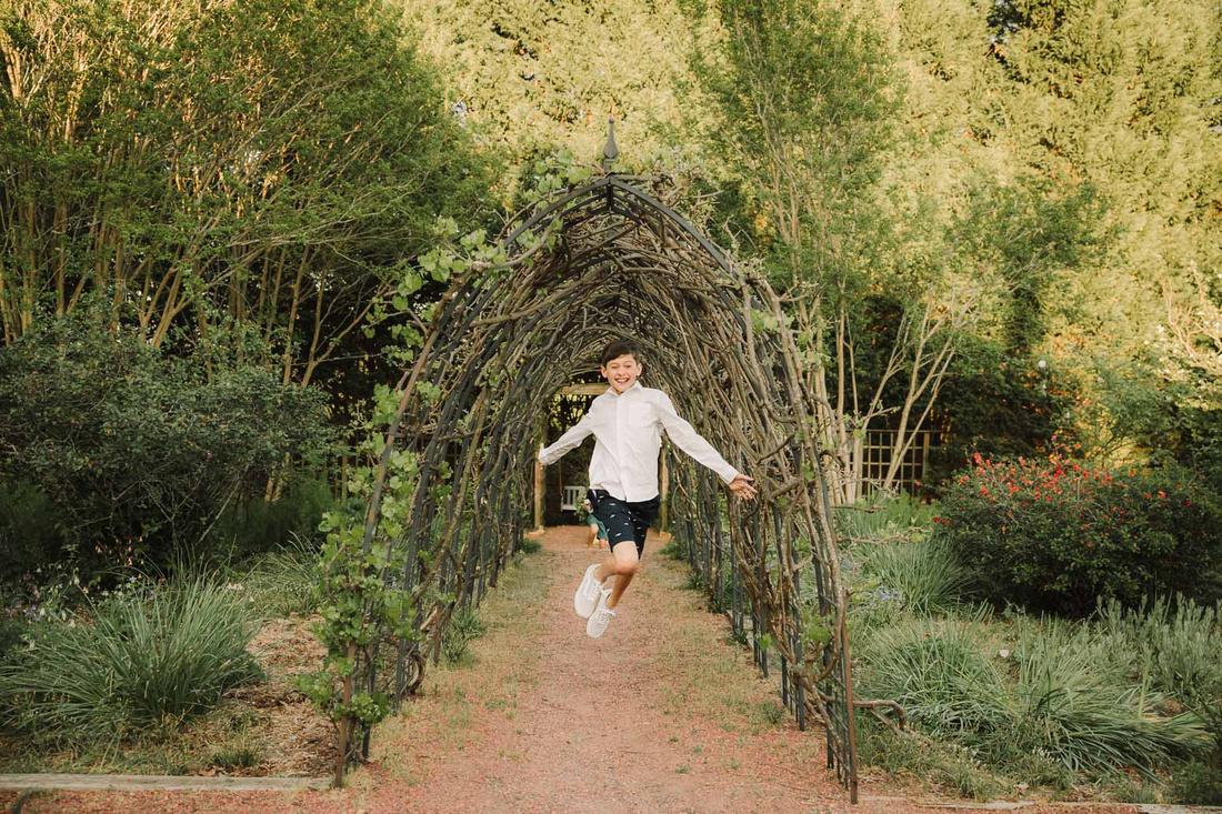 middle school boy running through a grape leaf tunnel at Barrington Hall