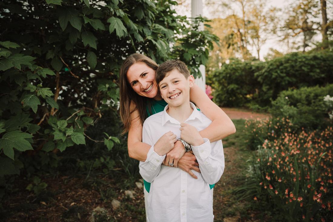 mothe hugs her happy tween son from behind