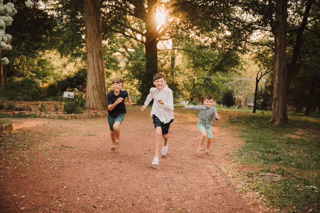 three brothers run through the grounds of Barrington hall during a family photo session