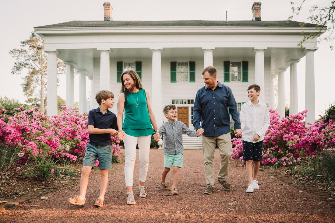 sprintime image of a family walking by azeleas bushes with historic barrington hall in the back ground
