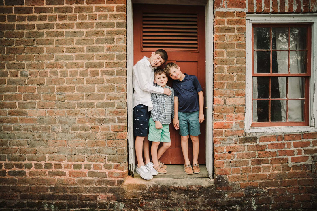 brothers standing in the door frame of the brick ice house on the grounds of Barrington Hall