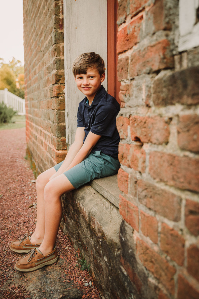 Smirking young boy sitting in a dorrframe during a family photo session