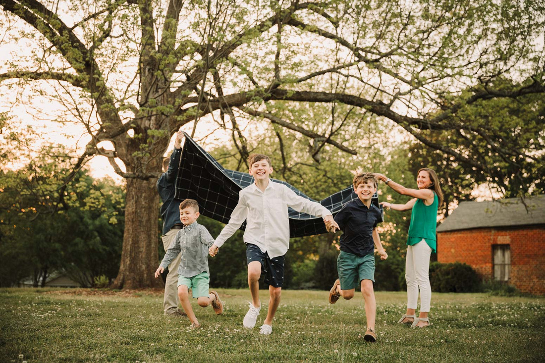three happy brother play a game with their parents and a blanket by monica carlson