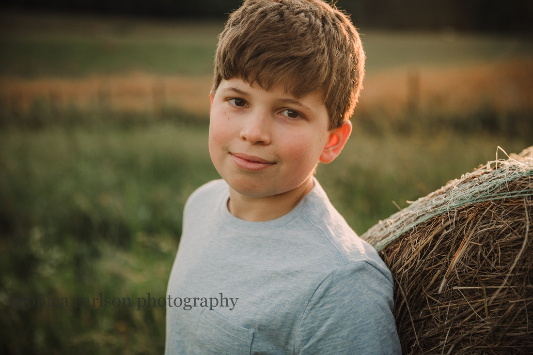 smiling teen boy leans on a bale of hay by monica carlson photography