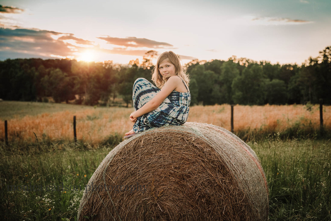 young girl smiles while siting on a haybale at sunset at Prospect farms
