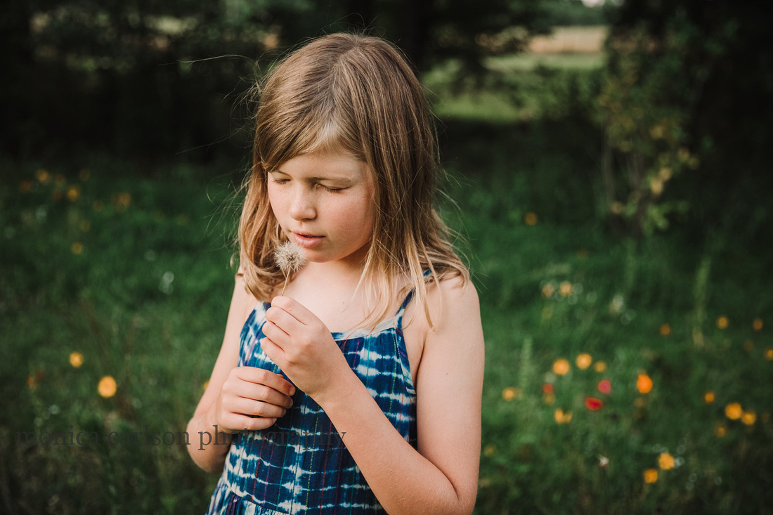 yound girl closes her eyes before blowing a dandelion by monica carlson