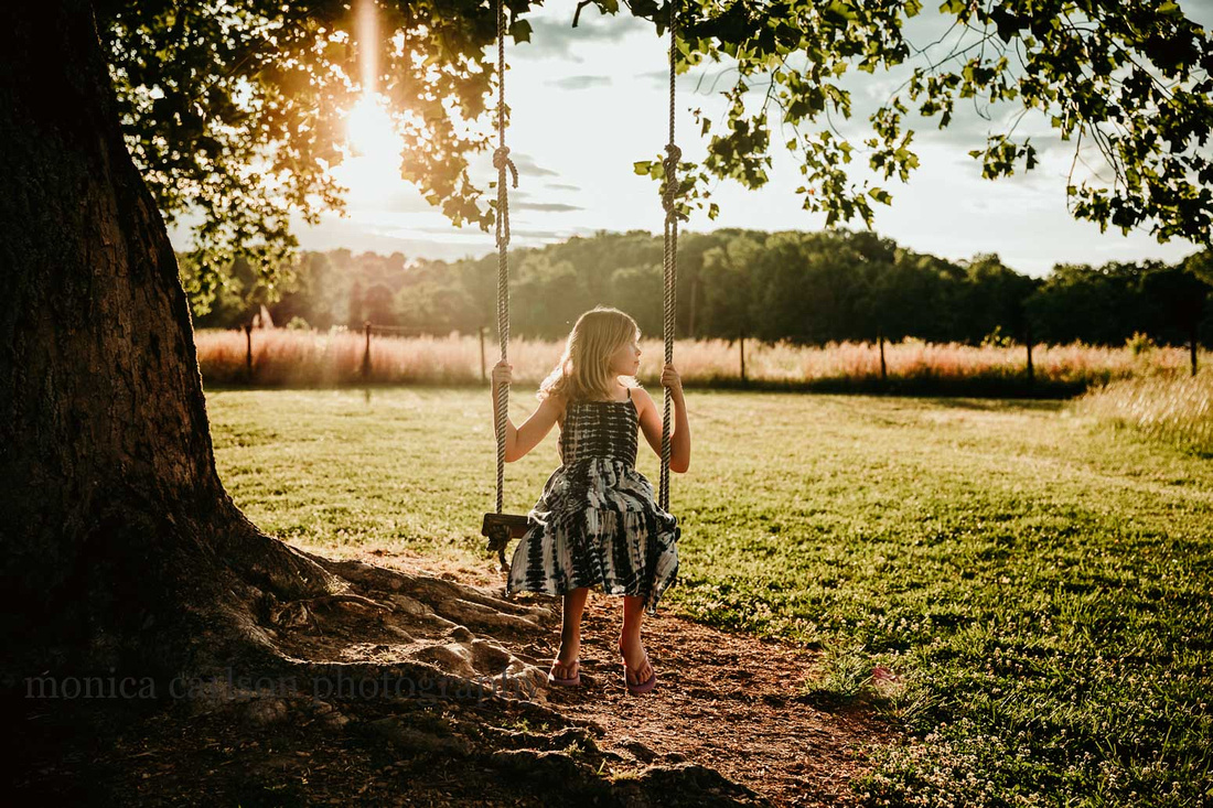 Young girl on a tree swing with the sun setting behind her by monica carlson photography