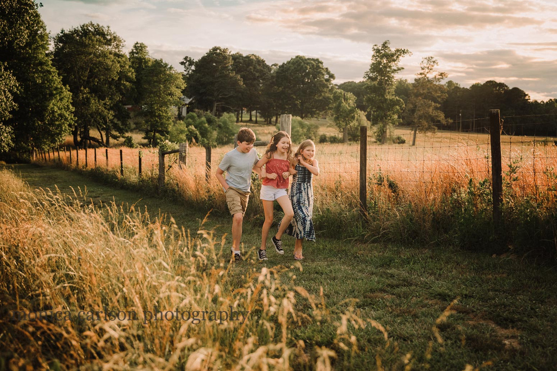 three siblings walking arm and arm on a farm in Lawerenceville, Ga