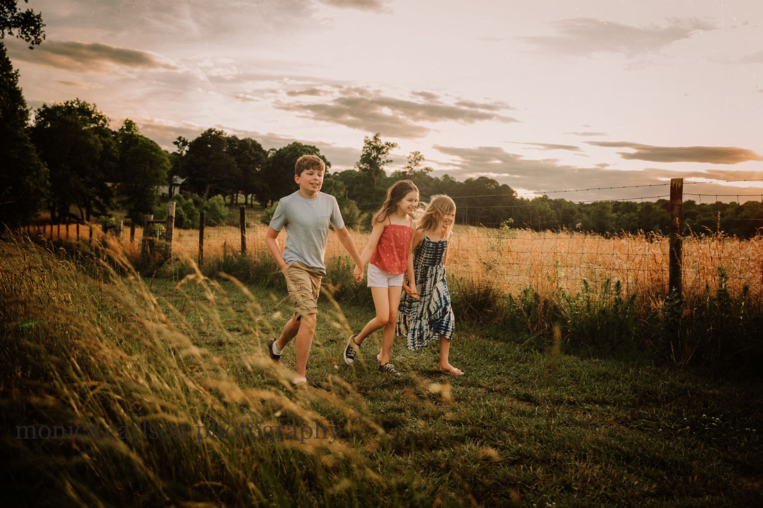 three happy kids walking together pn a farm with the sun setting behind them