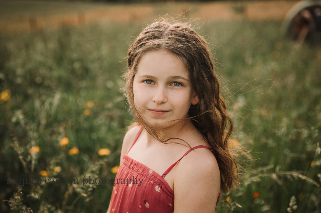 portrait of a blue eyed tween on a wildflower field by monica carlson photography