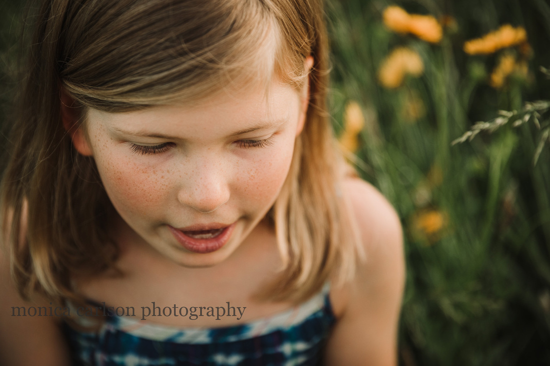 detailed image of a girls freckles and eye lashes who is sitting on a flower field