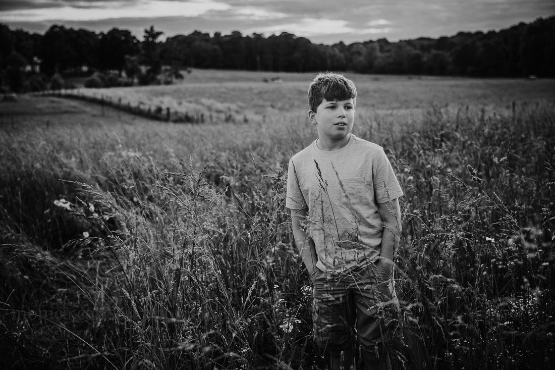 black and white image of a teen boy looking into the distance wihile on a field in Lawernceville