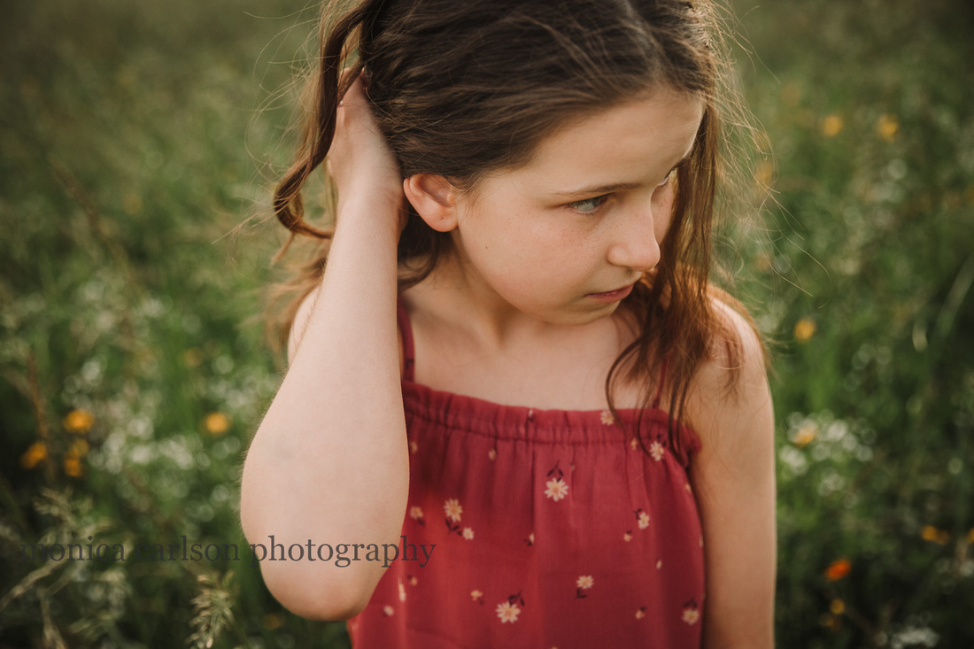 tween girl pushing her cruly brown hair away from her face while standing in a field of flowers