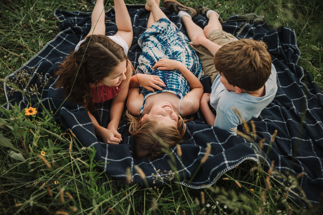 siblings laying together on a blanket in a field at prospect farms