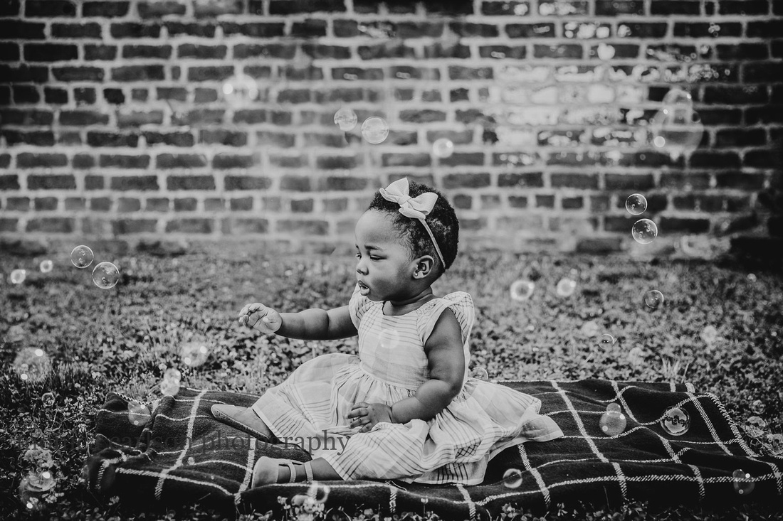 black and while image of a little girl sitting on a blanket and reaching out for bubbles by monica carlson