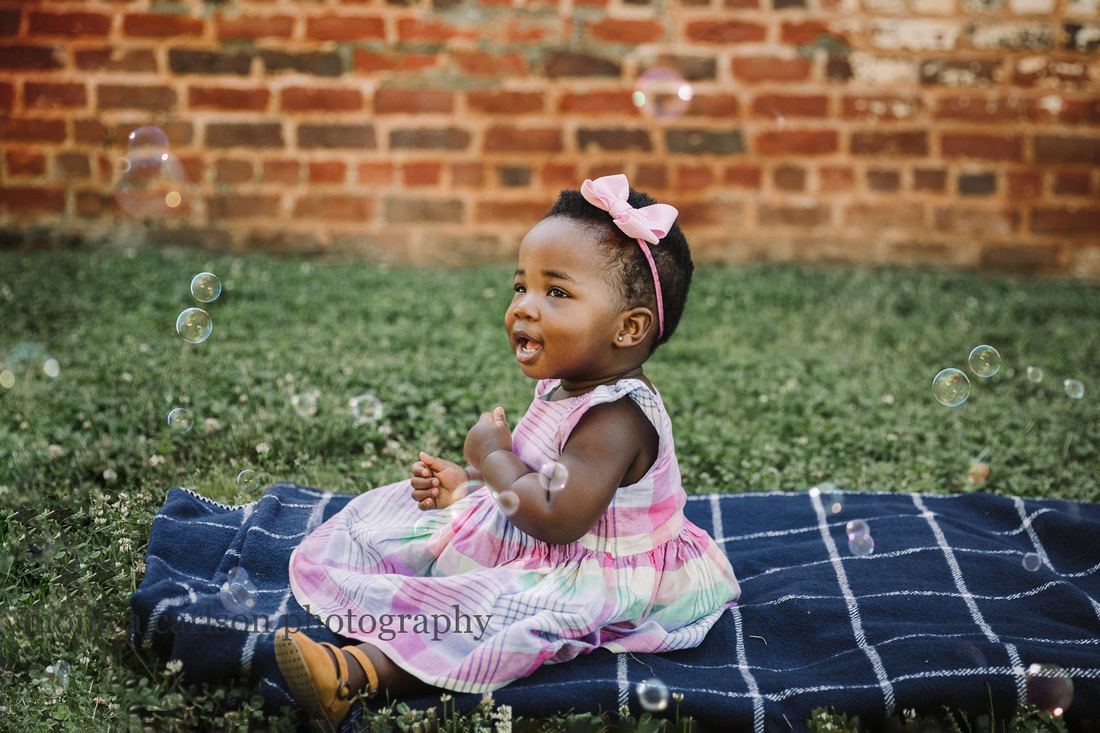 happy african american baby girl plays with bubbles while sitting on a blanket during a family photo session in roswell, GA
