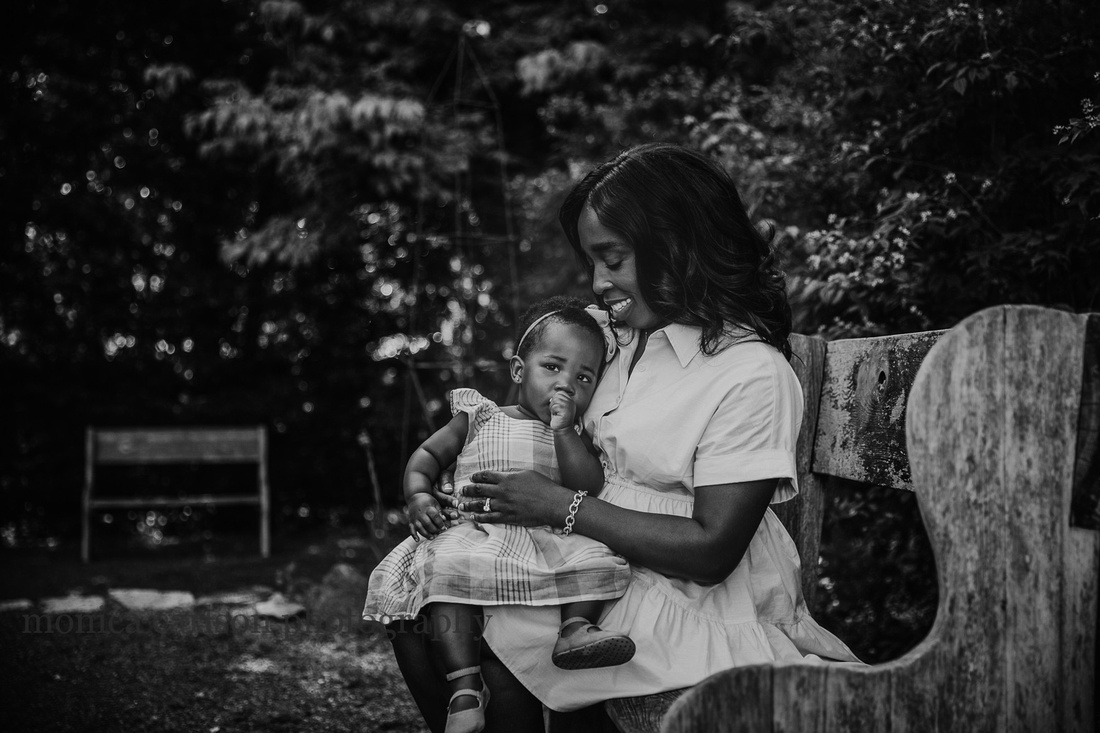 black and white image of a baby being held in her mothers lap while sitting in a garden during a family photo session