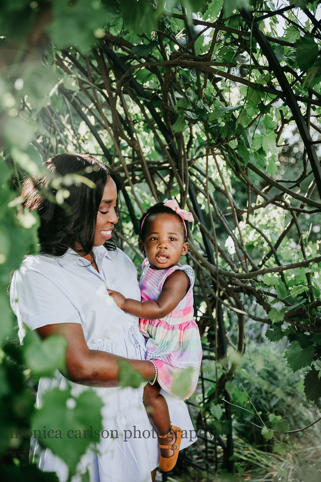 mother holds her baby girl happily in a grape vine tunnel during a photo session in Roswell, GA with Monica carlson photography