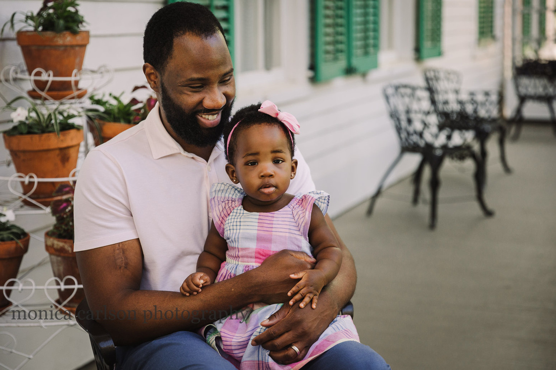 father laughs with is one year old daughter sitting on his lap on the patio of Barrington Hall