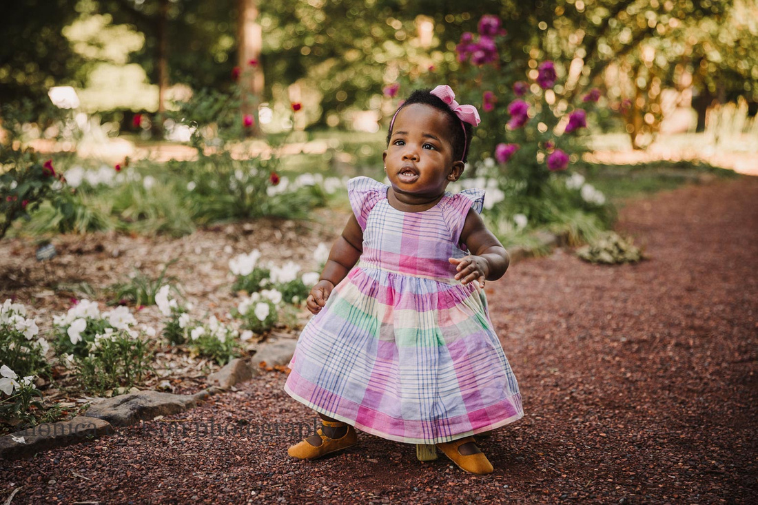 chubby one year old wearing a pretty pastel party dress sits on a stool in a garden
