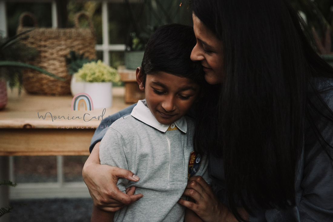mom and son share a tender moment in a greenhouse during a photo session with monica carlson