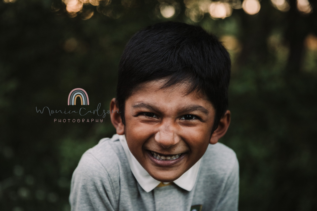 young, indian boy in a collared giggles for monica carlson photography