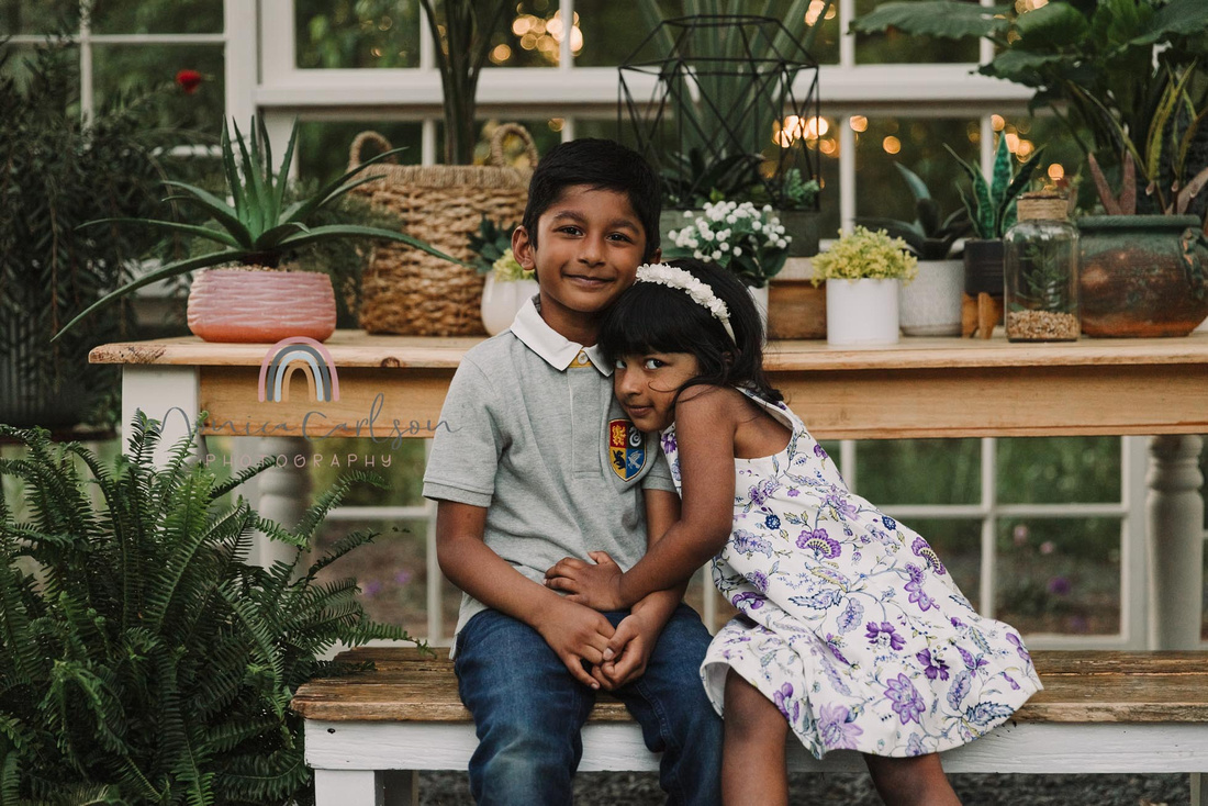 brother and sister hug inside the greenhouse at prospect farms by monica carlson